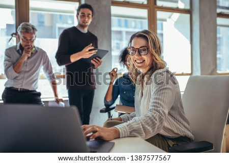 Female entrepreneur working on laptop and explaining strategy to attract followers to online web store while having meeting with colleagues in office. Royalty-Free Stock Photo #1387577567
