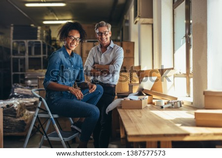 Smiling business partners together at online seller warehouse. Young woman and mature man looking at camera and smiling at drop shipping business office. #1387577573