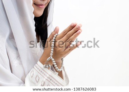 Hands of Asian muslim woman wearing prayer beads  welcoming guests / Ied Fitr Greeting in white background #1387626083