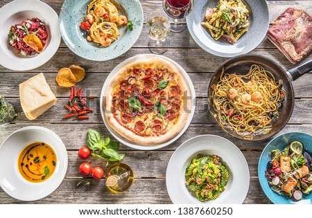 Top of view full table of italian meals on plates and pan. Pizza pasta risotto soup and fish vegetable salad. #1387660250