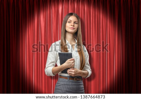 Front crop view of young attractive businesswoman holding daily planner standing in spotlight against red stage curtain. Planning and tactics. Business leadership. New ideas and approaches. #1387664873