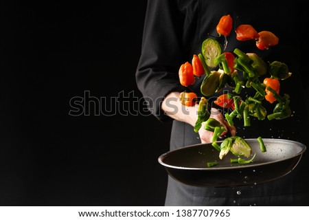 Chef preparing vegetables in a pan, Asian cuisine, on a black background for design, recipe book, menu, restaurant or hotel sign, cooking, gastronomy #1387707965