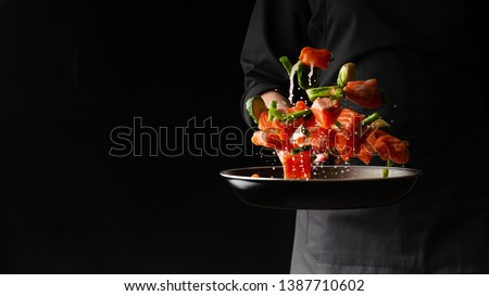 Sea cuisine, Professional cook prepares pieces of red fish, salmon, trout with vegetables.Cooking seafood, healthy vegetarian food and food on a dark background. Horizontal view. Banner #1387710602