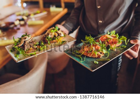 Two meat plate with salad leaves and summer salad in waiter's hand. #1387716146