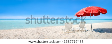 Beach panorama with sun chairs and parasol as background image Royalty-Free Stock Photo #1387797485