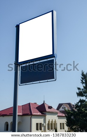 Empty square signboard placard outside on metallic pole with urban residential view in background. Blank white board outdoor with large copy space for your text or graphic design #1387833230