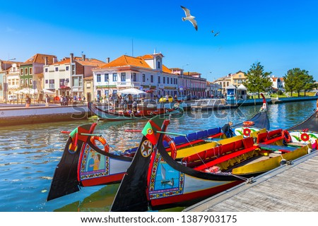 Traditional boats on the canal in Aveiro, Portugal. Colorful Moliceiro boat rides in Aveiro are popular with tourists to enjoy views of the charming canals. Aveiro, Portugal.  #1387903175