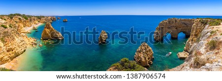 Natural caves at Marinha beach, Algarve Portugal. Rock cliff arches on Marinha beach and turquoise sea water on coast of Portugal in Algarve region.  Royalty-Free Stock Photo #1387906574