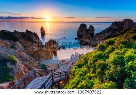 Camilo Beach (Praia do Camilo) at Algarve, Portugal with turquoise sea in background. Wooden footbridge to beach Praia do Camilo, Portugal. Wonderful view of Camilo Beach in Lagos, Algarve, Portugal. #1387907822