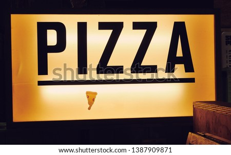 A trendy iconic cinematic typist font new york pizza sign inside a retro vintage hipster pizza diner in a city. Pop up eatery style pizza counter.