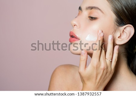 Skin cream concept. Facial care for female. Keep skin hydrated regularly moisturizing cream. Fresh healthy skin concept. Taking good care of her skin. Beautiful woman spreading cream on her face. #1387932557