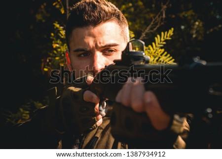 Hunter with shotgun gun on hunt. Hunter Target with laser sight. Collimating sight. Pulled the trigger of the shotgun. Close up Portrait of hamdsome Hunter #1387934912