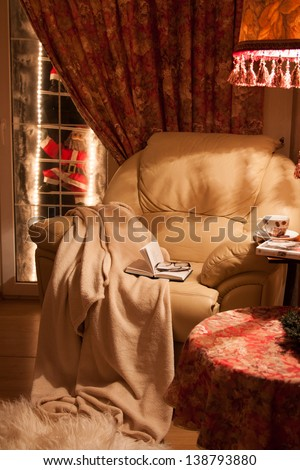 Cozy interior of the house.  A comfortable chair with a blanket, a book and a coffee. #138793880