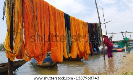 Hoian.Quang Nam / Vietnam - 04 30 2019: Woman standing with colorful fishing net #1387968743