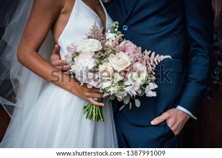 Wedding bouquet of white and pink roses and with newlywed couple #1387991009