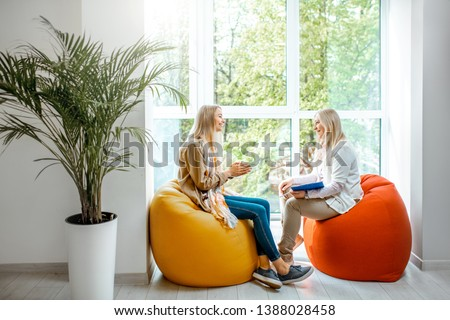 Young woman with senior female psychologist or mental coach sitting on the comfortable chairs during the psychological counseling in the office Royalty-Free Stock Photo #1388028458