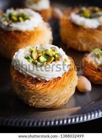 Kataifi, kadayif, kunafa, baklava pastry nests cookies with pistachios with tea. Cooking sweets turkish, or arabic traditional ramadan pastry dessert on a dark background. #1388032499