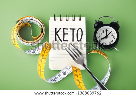 Keto word on notebook with clock fork and measuring tape around, intermittent fasting on keto concept #1388039762