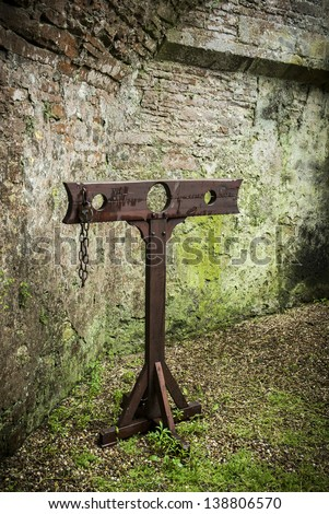 Detail of wooden medieval stocks used to incarcerate criminals in castle grounds.