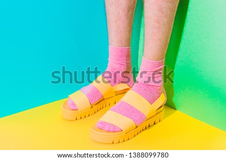 Male hairy legs in socks staying in women's sandals on bold background in the corner with strong shadows. Minimal pride concept. Body part #1388099780