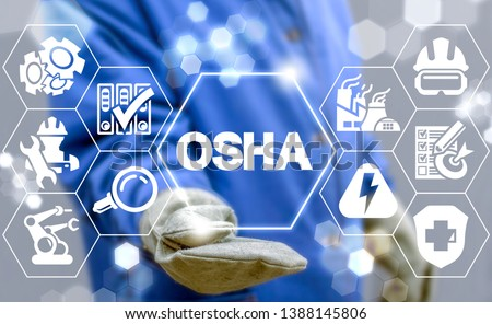 Industrial manager uses on a virtual screen of the future and sees the acronym: OSHA. OSHA - Occupational Safety and Health Administration Industry concept. #1388145806