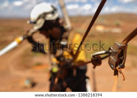 Defocused pic of rope access worker using industry secondary safety backup device on static twin ropes abseiling descending hanging fall arrest position while conducting safety fire watch mine site