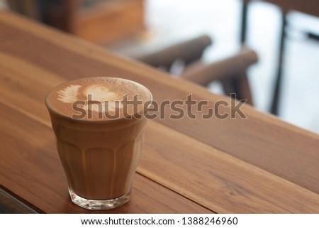 Piccolo Latte art in small glass on wooden desk. #1388246960