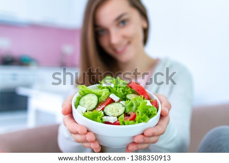 Healthy vegan woman holding a bowl of fresh vegetable salad. Balanced organic diet and clean eating. Healthy lifestyle #1388350913