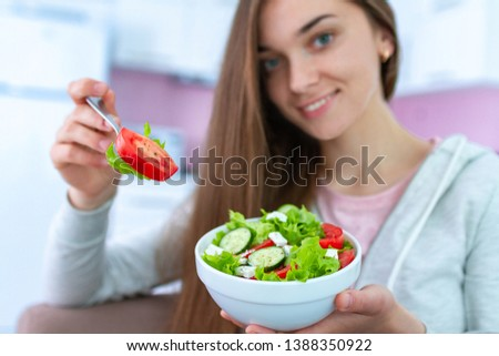 Portrait of young happy woman eating fresh vegetable salad at home. Balanced diet and fitness eating. Clean and control food. Healthy lifestyle #1388350922