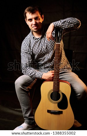 Young man playing acoustic guitar on grey background #1388355002