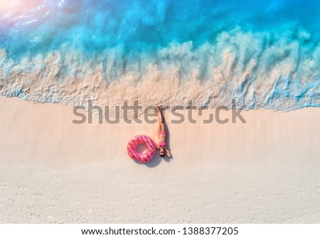 Aerial view of the beautiful young lying woman with pink donut swim ring on the white sandy beach near sea with waves at sunset. Summer holiday. Top view of slim girl, clear azure water. Indian Ocean #1388377205