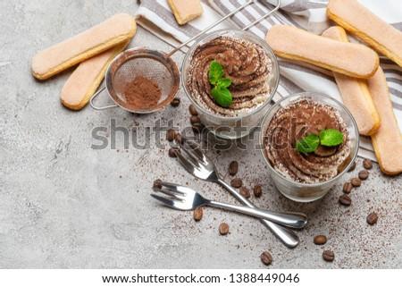 two portions Classic tiramisu dessert in a glass on concrete background #1388449046