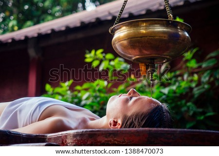 ayurveda massage alternative healing therapy.beautiful caucasian female getting shirodhara treatment lying on a wooden table in India salon #1388470073