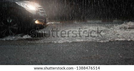 Car with headlights run through flood water after hard rain fall at night. #1388476514