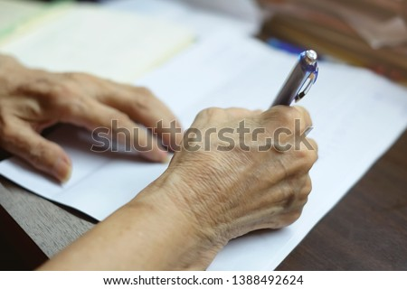 Selective focus at elderly hand using blue pen to writing letter. concept taking note and memorial. Write the letter, Low technology, Send and Receive letter, Retirement, testament signature and law #1388492624