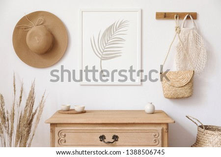 Stylish korean interior of living room with brown mock up poster frame, elegant accessories, flowers, wooden shelf and hanging rattan bags and hat. Minimalistic concept of home decor. Template.  #1388506745