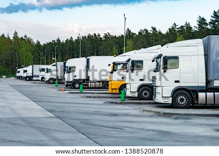 Trucks in a row with containers in the parking lot near forest , Logistic and Transport concept #1388520878