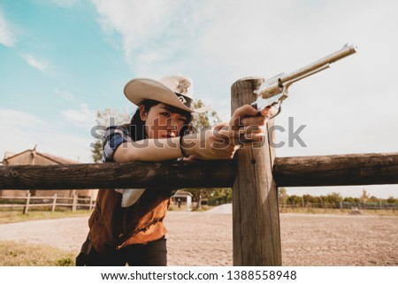 Portrait of a beautiful Chinese female cowgirl shooting with a weapon in the wild west behind a wooden fence