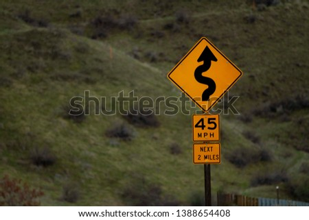 Road sign warning you to slow down as there will be a twisty road ahead #1388654408