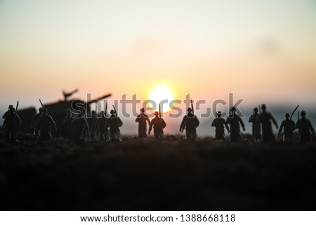 War Concept. Military silhouettes fighting scene on war fog sky background, World War Soldiers Silhouettes Below Cloudy Skyline at sunset. Attack scene. Armored vehicles. tank in action #1388668118
