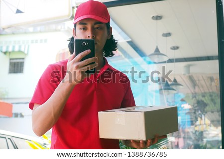 The young man sent the product to find the customer information via the smartphone. Fast delivery      #1388736785