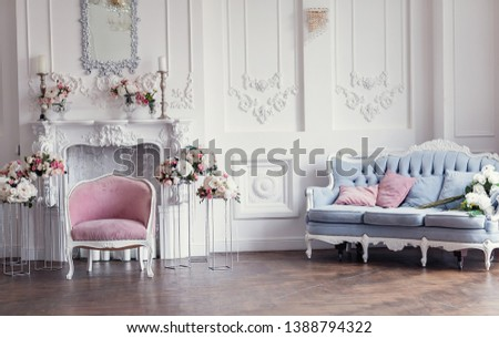 Elegant white fireplace full of flowers. Elegant white room decorated with easel and hat boxes. Wedding decorated area. Vintage decor in light interior