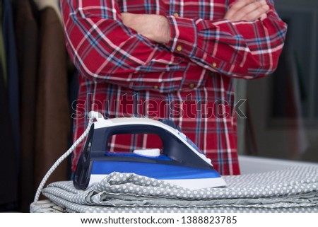 Man irons clothes on ironing board with blue iron. Housework and household concept #1388823785
