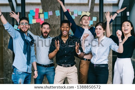 Young crew of happy excited male and female business partners celebrating completed startup project while looking at camera and laughing, overjoyed colleagues feeling amazed of done good work #1388850572