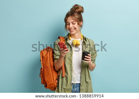Photo of positive young woman in casual clothes, downloads multimedia file on cell phone, has headphones on neck, holds disposable cup with cappuccino, carries backpack, isolated on blue wall #1388859914