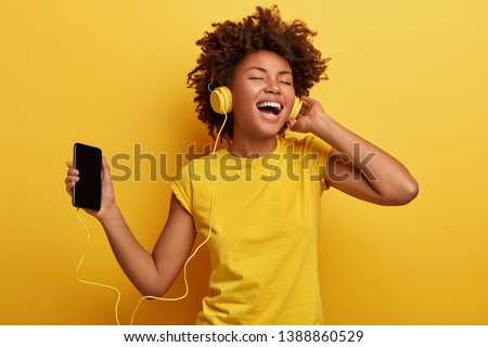 People, music, emotions concept. Delighted carefree female with Afro hairstyle dances in rhythm of melody, closes eyes listens loud song in headphones, holds smart phone has fun. Yellow color prevails #1388860529