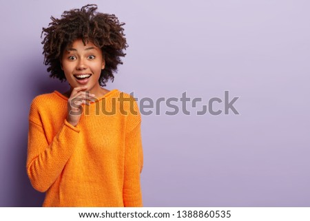 Beautiful woman with Afro hairstyle smiles gently at camera, touches chin, looks happily at camera, wears orange jumper, isolated over purple background with copy space aside for your promotion #1388860535