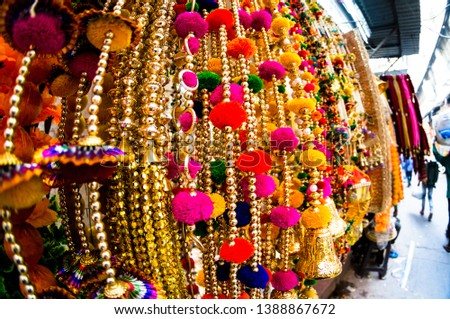 Dangling golden decorations with bells and puffs hanging in a store in chandni chowk delhi. These decorations are perfect for weddings, events, christmas and more. Shot with a fish eye lens it #1388867672
