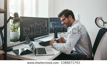 Lucky day. Happy young businessman or trader in formalwear and eyeglasses using laptop and smiling while sitting in his modern office #1388871743