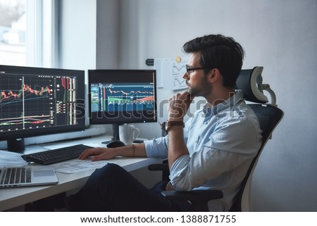 Busy working day. Side view of successful trader or businessman in formal wear and eyeglasses working with charts and market reports on computer screens in his modern office #1388871755